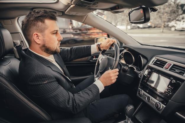 Autista caucasico bello dell'uomo d'affari dentro in veicolo