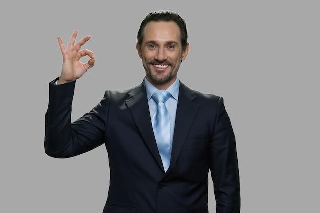 Uomo d'affari caucasico bello che gesturing bene con le dita. uomo con felice espressione facciale che guarda l'obbiettivo su sfondo grigio.