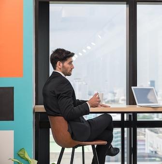 Uomo d'affari caucasico bello che si siede e che tiene una tazza di caffè durante la pausa in ufficio moderno