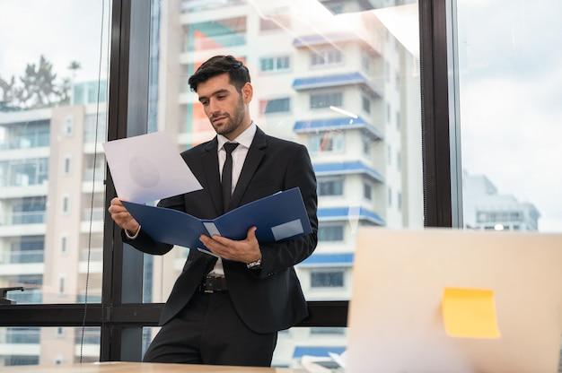 Bello imprenditore caucasico in piedi e analizzando la relazione finanziaria in un ufficio moderno al quartiere degli affari