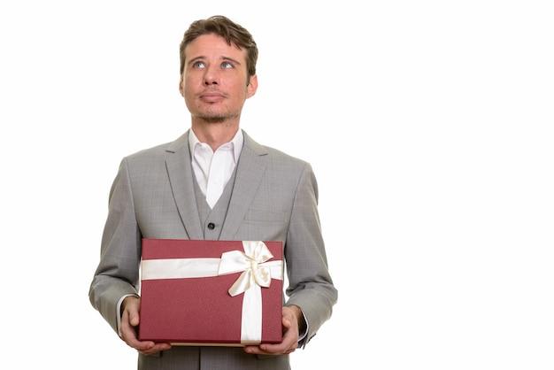Uomo d'affari caucasico bello che pensa mentre tiene il contenitore di regalo