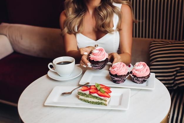 Bella femmina caucasica con lunghi capelli biondi ondulati si siede sul divano, beve caffè e mangia deliziosi cupcakes rosa in cucina