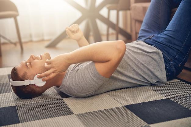 Bel ragazzo caucasico che si rilassa sul tappeto mentre ascolta la musica con le cuffie bianche