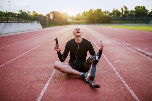 Giovane sportivo handicappato caucasico bello vestito in abiti sportivi e con la gamba artificiale che si siede sulla pista, ascoltando musica su smart phone e cantando.