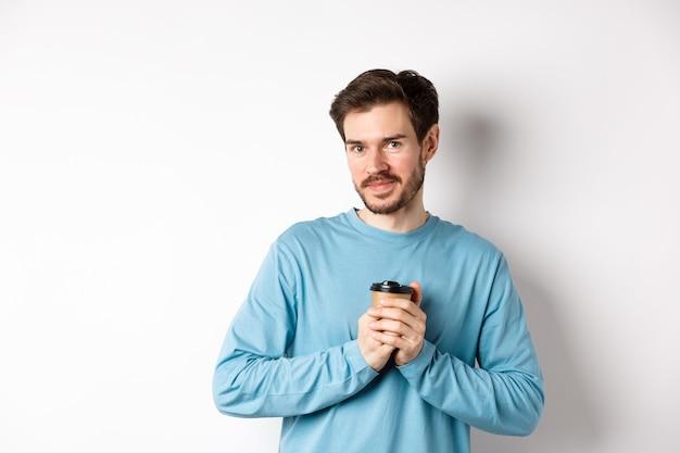 Bell'uomo caucasico warm-up mani con una tazza di caffè, sorridendo alla telecamera e guardando teneramente, in piedi su sfondo bianco.