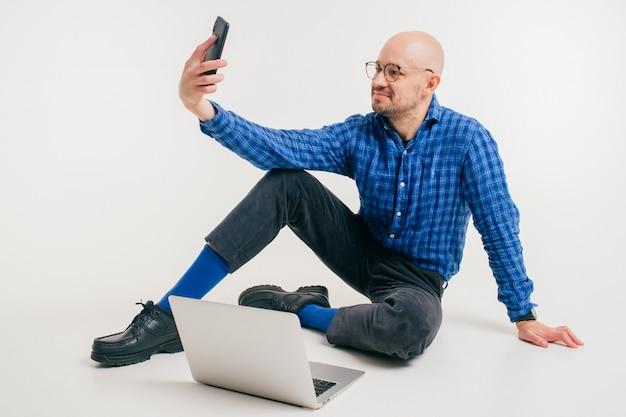 L'uomo caucasico bello senza capelli in camicia blu, pantaloni neri e calzini blu fa il libero professionista con il computer portatile e fa il selfie.