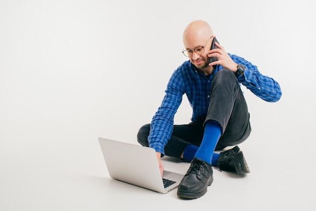 L'uomo caucasico bello senza capelli in camicia blu, pantaloni neri e calzini blu fa il libero professionista con il computer portatile e parla sul telefono