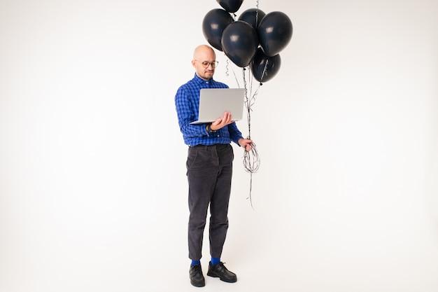 Uomo caucasico bello senza capelli in camicia blu, pantaloni neri e calzini blu con laptop e palloncini neri nelle sue mani