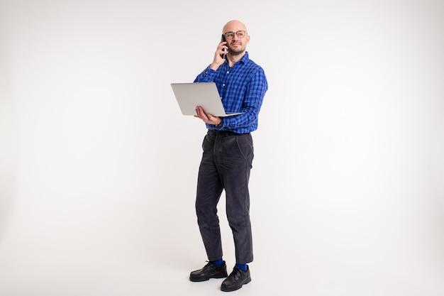 L'uomo caucasico bello senza capelli in camicia blu, pantaloni neri e calzini blu funziona con il computer portatile