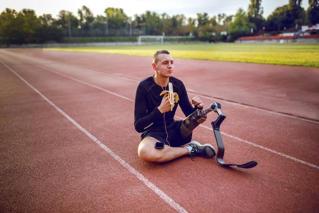 Giovane handicappato sportivo caucasico bello in abbigliamento sportivo e con la gamba artificiale che si siede sulla pista, ascoltando musica e mangiando una banana.