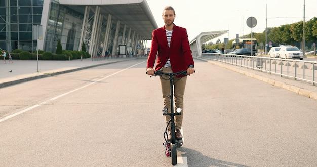 Bello giovane uomo alla moda caucasico in giacca rossa in piedi su scooter elettrico in strada urbana vicino al grande edificio moderno. cavaliere maschio che va dalla città sulla strada. giorno soleggiato.