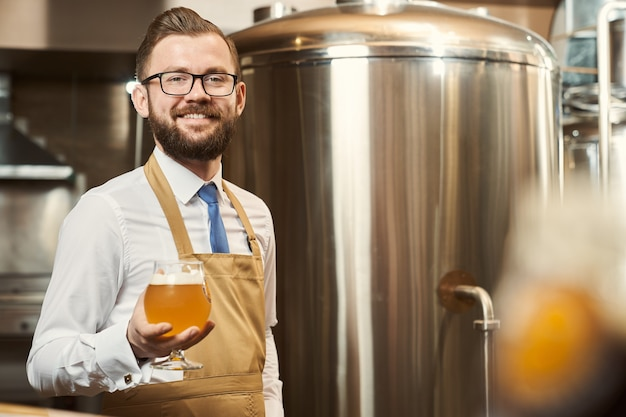 Birraio bello e allegro in camicia bianca e grembiule marrone in piedi, tenendo in mano un bicchiere di birra fredda con schiuma. positivo sorridente professionale, in posa sullo sfondo del serbatoio di stoccaggio.