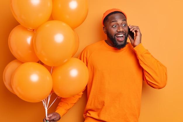 Bell'uomo allegro ha sorrisi di conversazione telefonica ampiamente vestito con indifferenza arriva alla festa di compleanno tiene un mazzo di palloncini arancioni esprime pura felicità