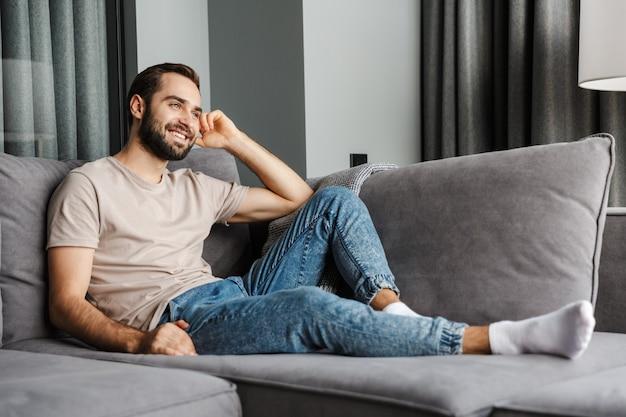 Un bel giovane uomo positivo allegro al chiuso a casa seduto sul divano.