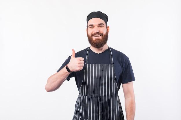 Uomo bello del cuoco unico con la barba che mostra pollice sul gesto