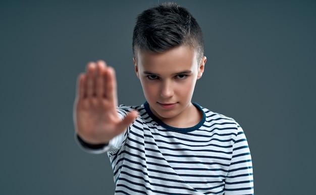 Bel bambino infastidito dal cattivo atteggiamento che fa il segnale di stop con la mano, dicendo di no, esprimendo sicurezza, difesa o restrizione isolata su grigio.