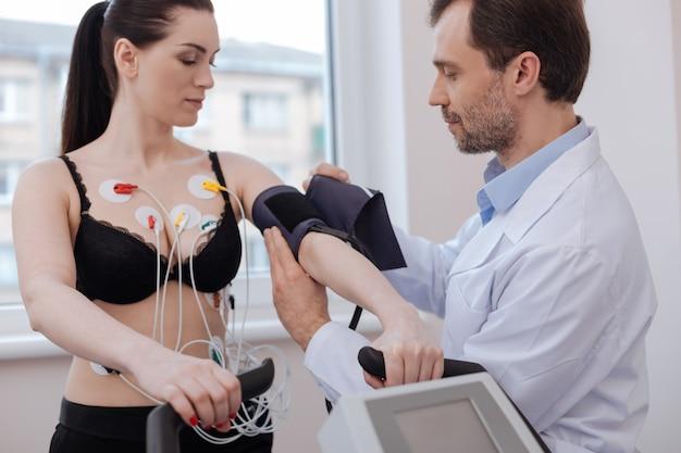 Bello intelligente distinto rendendo il suo paziente che indossa diversi pezzi di equipaggiamento mentre conduce una diagnostica