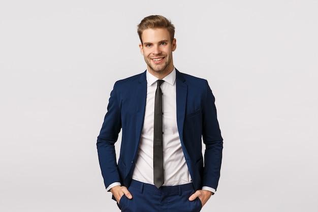 Bell'uomo d'affari barbuto biondo fiducioso, con le mani in tasca, sorridente con gioia, dà atmosfera professionale, discute di affari, raddoppia il suo reddito, diventa di successo, sfondo bianco
