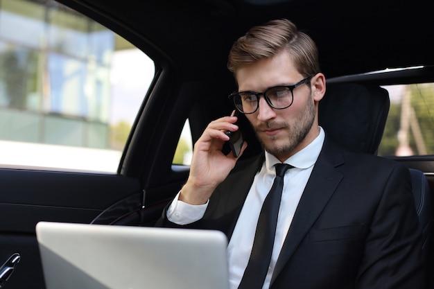 Bell'uomo d'affari fiducioso in tuta che parla allo smartphone e lavora utilizzando il laptop mentre è seduto in macchina.