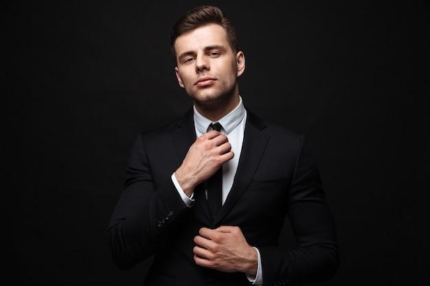 Uomo d'affari fiducioso bello che indossa tuta in piedi isolato sul muro nero, in posa