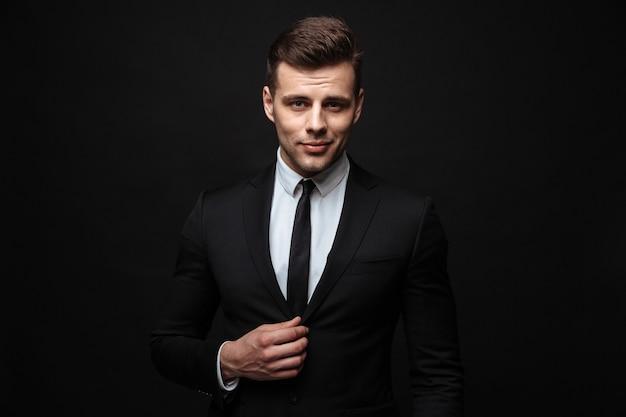 Un bell'uomo d'affari fiducioso che indossa un abito in piedi isolato su un muro nero
