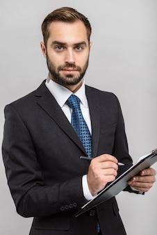 Un bell'uomo d'affari fiducioso che indossa un abito in piedi isolato su un muro grigio, con in mano un blocco note, notando