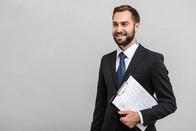 Un bell'uomo d'affari fiducioso che indossa un abito in piedi isolato su un muro grigio, con in mano un blocco note