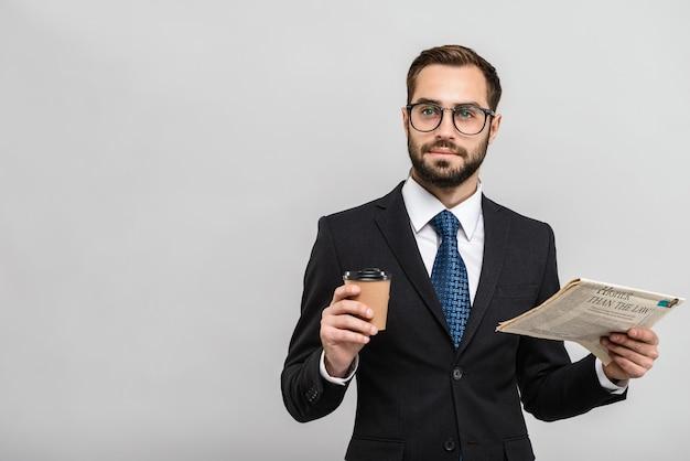 Un bell'uomo d'affari fiducioso che indossa un abito in piedi isolato su un muro grigio, legge il giornale, beve caffè da asporto