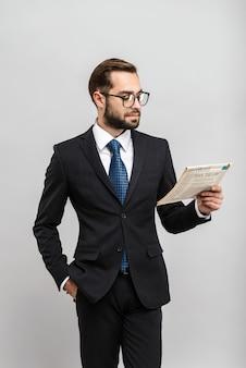 Un bell'uomo d'affari fiducioso che indossa un abito in piedi isolato su un muro grigio, legge il giornale, indossa gli occhiali