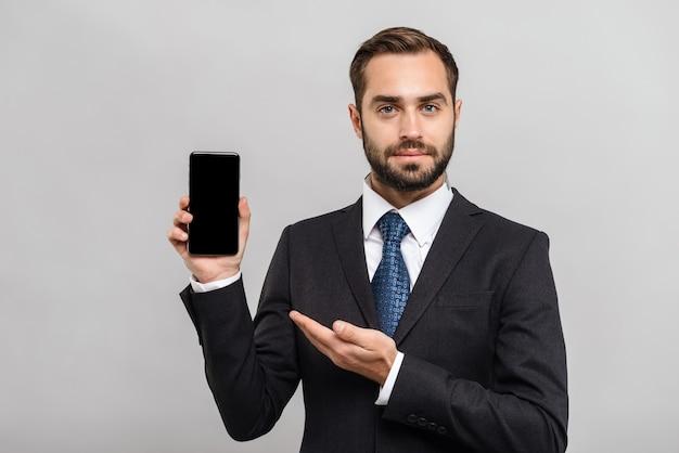 Un bell'uomo d'affari fiducioso che indossa un abito in piedi isolato su un muro grigio, che mostra un telefono cellulare con schermo vuoto