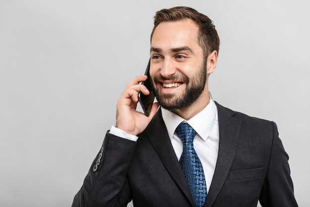 Un bell'uomo d'affari fiducioso che indossa un abito in piedi isolato su un muro grigio, parlando al telefono cellulare