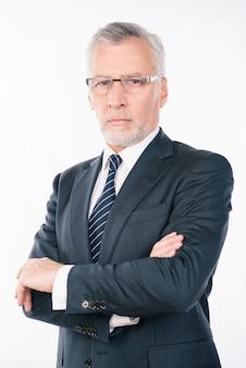 Bello imprenditore fiducioso con barba grigia e occhiali che attraversano le mani