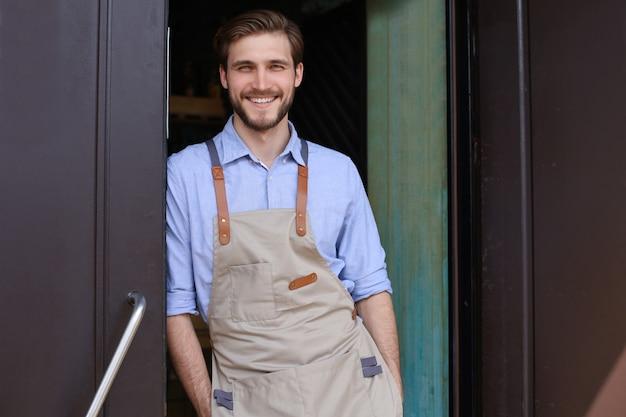Proprietario del caffè bello e fiducioso in piedi davanti alla porta. giovane uomo in piedi con le braccia incrociate guardando sorridente della fotocamera.