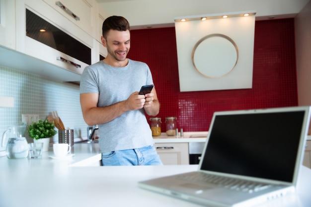 L'uomo moderno fiducioso bello in maglietta grigia sta con il telefono in mano e beve il caffè dalla tazza gialla sulla cucina a casa