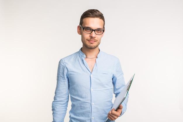 Bel uomo serio fiducioso in bicchieri in piedi sul muro bianco.
