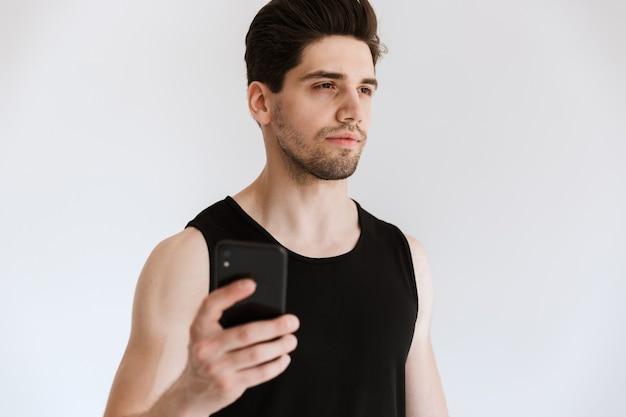 Bello sportivo fiducioso che tiene il telefono cellulare mentre si trova isolato su un muro bianco