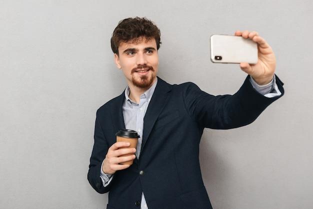 Bel giovane imprenditore fiducioso che indossa una giacca in piedi isolato su grigio, prendendo un selfie, tenendo la tazza di caffè da asporto