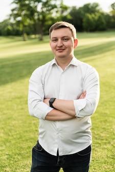 Un bel giovane fiducioso in piedi e sorridente in una camicia bianca.