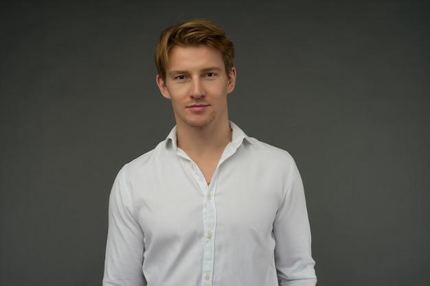 Un bel giovane uomo sicuro di capelli rossi in piedi e sorridente in una camicia bianca.