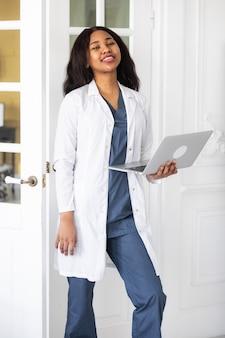 Medico femminile afroamericano contento bello che lavora ad una telemedicina del computer portatile