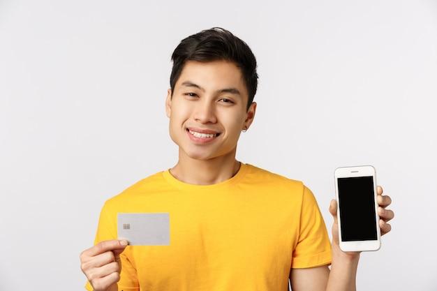 Uomo asiatico sorridente bello e carino in maglietta gialla, che mostra il display del telefono e la carta di credito, sorridendo felice, consiglia servizio bancario, sistema di pagamento online, muro bianco in piedi