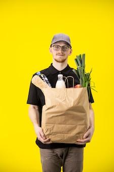 Uomo di consegna bello che trasporta sacchetto di carta di cibo