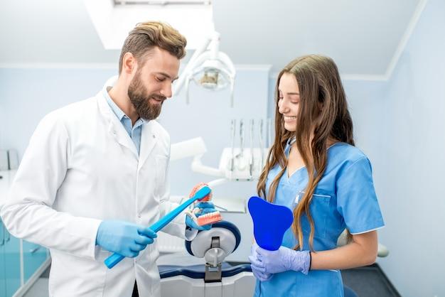 Bel dentista che mostra come lavarsi i denti sulla mascella artificiale alla giovane studentessa presso lo studio dentistico
