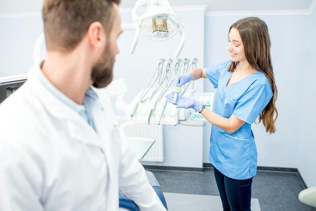 Bel dentista con giovane assistente femminile in uniforme che si prepara per il lavoro presso lo studio dentistico