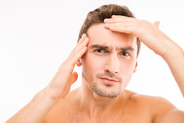 Giovane disturbato bello che tocca il suo fronte dopo la rasatura