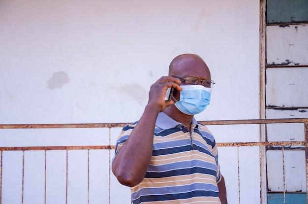Un bell'uomo africano anziano che indossa una maschera per il viso che impedisce a se stesso di scoppiare nella società sentendosi eccitato per la chiamata che sta facendo con il suo cellulare.