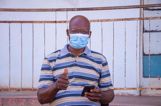 Un bell'uomo africano anziano che indossa una maschera per il viso che previene, si è impedito di scoppiare nella società sentendosi eccitato per ciò che ha visto sul suo cellulare e ha fatto il pollice in alto