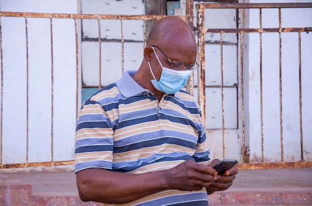 Un bell'uomo africano anziano che indossa una maschera facciale che impedisce a se stesso di scoppiare nella società sentendosi eccitato per ciò che ha visto sul suo cellulare.