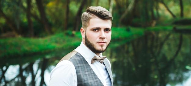 Lo sposo barbuto bello ed elegante in abito a scacchi è in piedi sul ponte nella foresta. foto alla moda degli sposi del matrimonio. ritratto di hipster rustico.