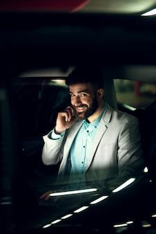 Bell'uomo d'affari elegante sta guardando attraverso il finestrino dell'auto mentre parla su un cellulare.